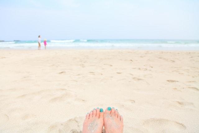 綺麗な爪と砂浜の画像-